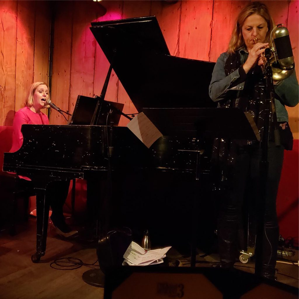 Brenda playing piano and singing with Ingrid Jenson on trumpet